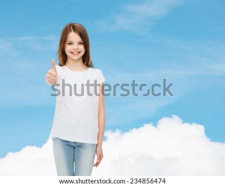 advertising, dream, childhood, gesture and people - smiling little girl in white blank t-shirt showing thumbs up over blue sky background - stock photo