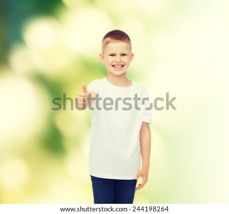 advertising, ecology, gesture, people and childhood concept - smiling boy in white blank t-shirt showing thumbs up over green background - stock photo