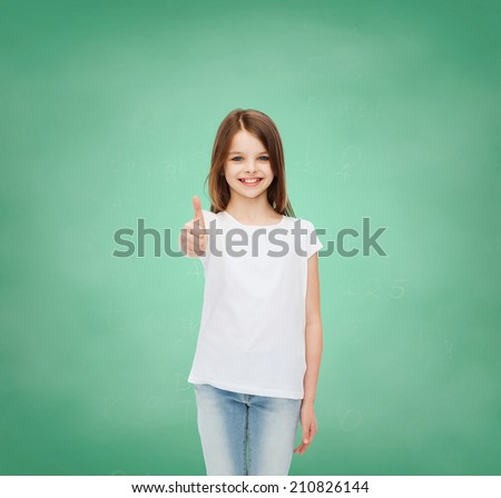 advertising, gesture, education, childhood and people - smiling little girl in white t-shirt showing thumbs up over green board background - stock photo