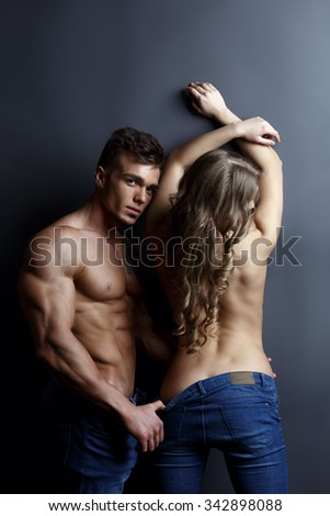 Advertising jeans. Tanned models posing topless - stock photo