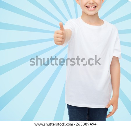 advertising, people and childhood concept - close up of smiling little boy in white blank t-shirt showing thumbs up over blue burst rays background - stock photo