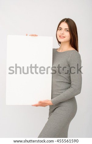 Advertising. Woman in black dress. Smiling woman showing blank card or paper on white background.