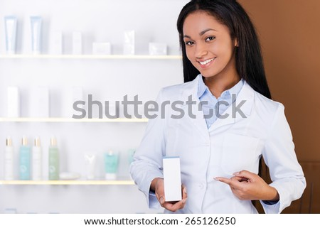 Advertising your product. Beautiful young African woman in lab coat holding container with some medicine and pointing it with smile while standing in drugstore  - stock photo