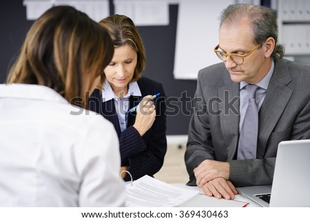 Adviser explaining paperwork to a middle-aged couple at a meeting in her office as they concentrate on the documents