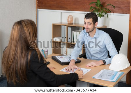 Adviser sitting in a meeting on the table explaining something his colleague. - stock photo