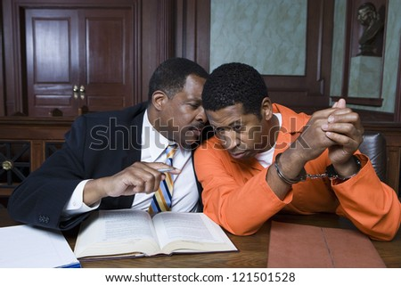 Advocate discussing a point with arrested man while sitting in the courtroom - stock photo