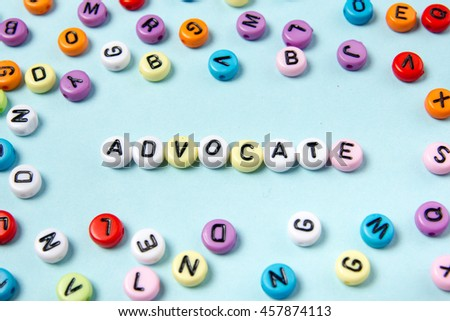 ADVOCATE word in a circle of abc colorful letters on blue desk table background.  Invitation in team.