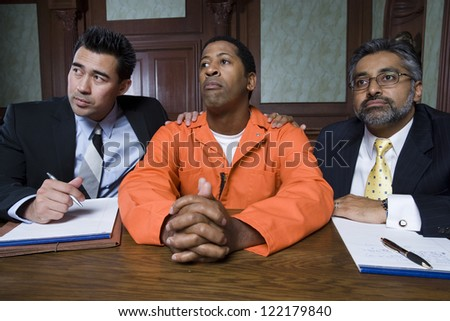 Advocates and client listening to case in courtroom - stock photo