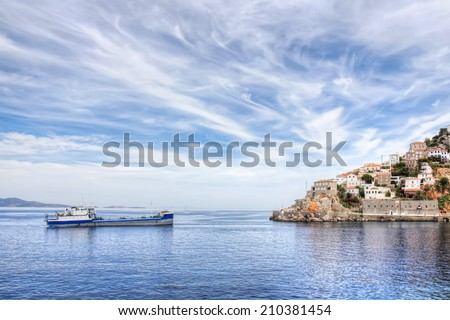 Aegean Sea and Greek island of Hydra or Ydra, a ship, and a dramatic blue and white cloudy sky in the Saronic Gulf, Aegean Sea, Greece.