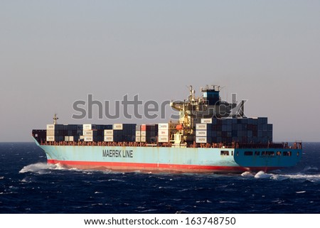 AEGEAN SEA, GREECE -SEPTEMBER 8: A containership at sea belonging to the Maersk Group.  Since 1996, Maersk is the largest container shipping company in the world on Sept 8, 2013, Aegean Sea in Greece