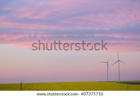 Aeolian field and wind turbines at sunset - stock photo