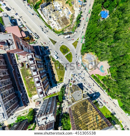 Aerial city view with crossroads and roads, houses, buildings, parks and parking lots, bridges. Urban landscape. Copter shot. Panoramic image. - stock photo