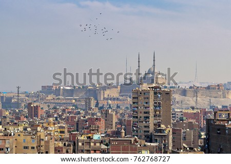 Aerial cityscape view of old Cairo, Egypt with old buildings and Citadel of Egypt in far distance from minaret of Ibn Tulun Mosque