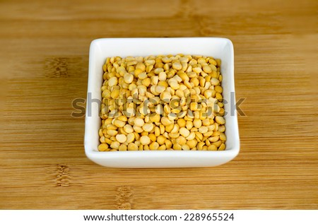 Aerial closeup of yellow split peas in white bowl - stock photo