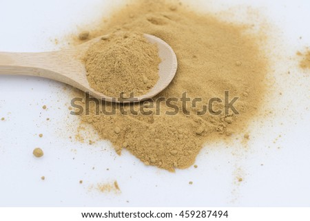 Aerial closeup view on dry ginger powder. Heap of spice powder with a scoop on the heap.  Isolated on white background.