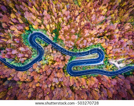 Aerial drone view of a curved winding road through the forest high up in the mountains
