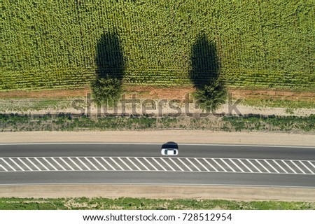 Aerial drone view of a highway passing through green fields