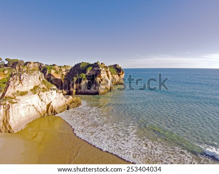 Aerial from rocks and ocean at Praia tres Irmaos in Algarve Portugal - stock photo