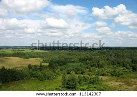 Aerial green meadows and forests view on blue sky with clouds background