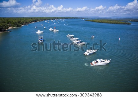Aerial image of a group of yachts lined up in the ocean close to the shoreline