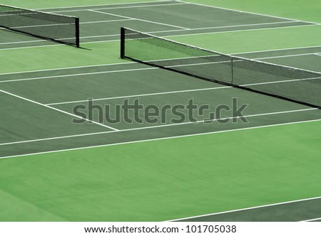 Aerial image of empty outdoor green hard tennis court with nets. - stock photo