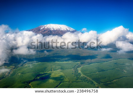 Aerial image of Mount Kilimanjaro, Africa's highest mountain, with snow and white puffy clouds from Kenya - stock photo