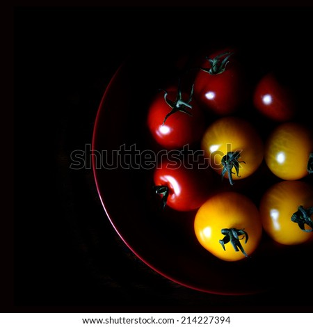 Aerial image of selectively lit amber & rosso vine tomatoes against black. Copy space. - stock photo