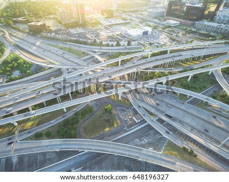 Aerial Interstate I-610 freeway with massive intersection, stack interchange, elevated road junction overpass and building. Nightly degree vertical view metropolitan area of mid-town Houston, Texas,US