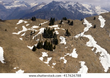 aerial landscape, from a small plane, of remains of snow over  late winter slope with meadows and firs , shot in Orobie mountains with Corte range in background, Bergamo , Italy - stock photo