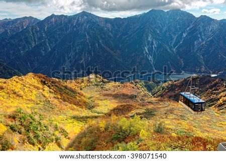 Aerial panorama of a scenic cable car flying over the beautiful autumn valley in Tateyama Kurobe Alpine Route, Toyama Japan ~ A magnificent view from Daikanbo over Kurobe dam & colorful autumn valley - stock photo