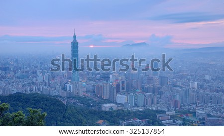 Aerial panorama of busy Taipei City at moody dusk with Taipei 101 in XinYi commercial area, Tamsui River and downtown area in twilight with beautiful rosy afterglow shining through heavy clouds  - stock photo
