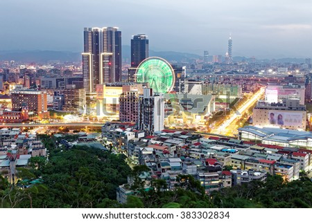 Aerial panorama of busy Taipei City in twilight with view of a giant ferris wheel in Dazhi Commercial District and taipei 101 in downtown area ~ A romantic night in Taipei, the capital city of Taiwan - stock photo