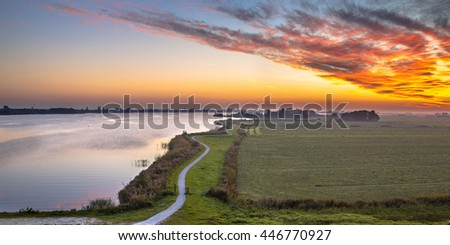 Aerial panorama of Netherlands Polder landscape with winding cycling track along river under beautiful sunset