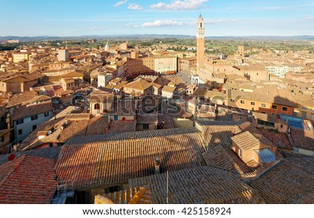 Aerial panorama of Siena, a beautiful medieval town in Tuscany Italy, with the famous landmark Mangia Tower ( Torre del Mangia ) standing tall by town square ( Piazza del Campo ) in city center - stock photo
