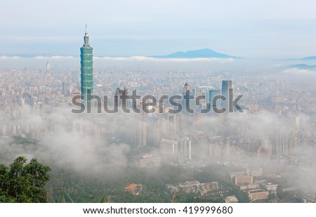 Aerial panorama of Taipei, the capital city of Taiwan, on a foggy spring morning with the prominent Taipei 101 Tower among skyscrapers in downtown, Tamsui River and mountains in the distant background - stock photo
