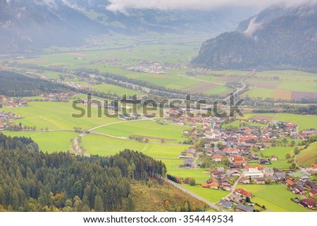Aerial panorama of towns and highways in a valley surrounded by Alpine mountains south of Achensee in Tirol, Austria ~ Idyllic landscape of Tirolean countryside - stock photo