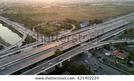 Aerial panoramic view of an intersection of the highway over the canal in Thailand with beautiful warm light of evening sunset. It is the left-hand traffic system.