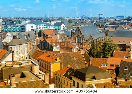 Aerial panoramic view of Ghent, Belgium with  roofs and traditional medieval buildings, church against cloudy blue sky - stock photo