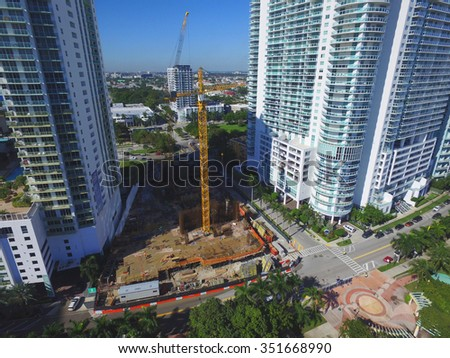 Aerial photo of a construction site between other highrise buildings - stock photo