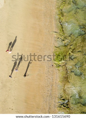 Aerial photo of a family walking past a fisherman on the beach with long shadows