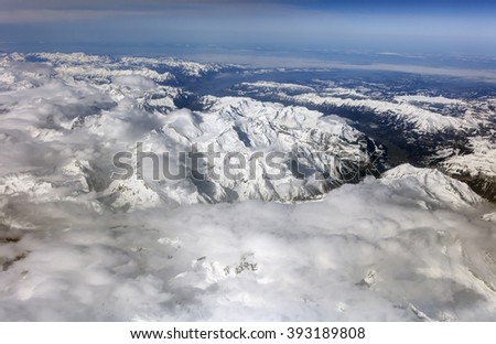 Aerial photo of the landscape with clouds, snowy mountains and view stretching all the way to the horizon