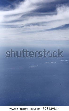 Aerial photo of the sea with clouds and view stretching all the way to the horizon