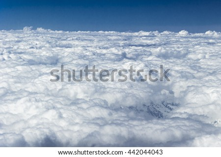 aerial photography over the Alps with clouds in the evening, from a commercial plane,
