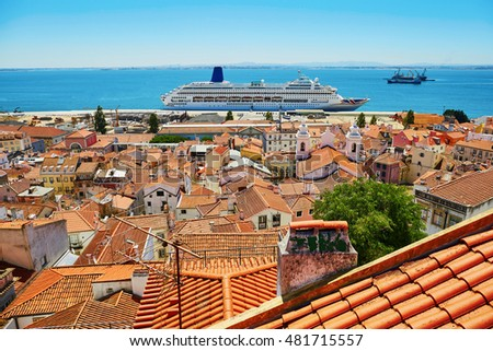 Aerial scenic view of central Lisbon, Portugal with red tile roofs, Tagus river and large cruise ship