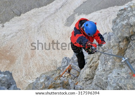 "Aerial section of via ferrata ""Merlone"" with climber woman high above valley, Cadini di Misurina, Dolomite Alps, Italy - stock photo"