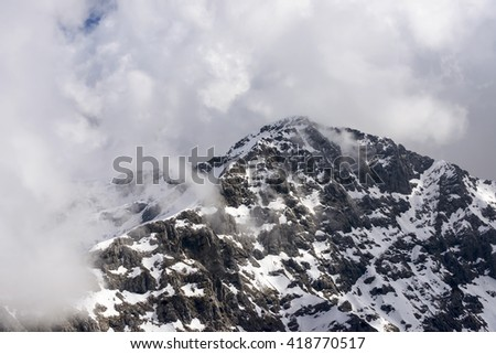 aerial shot, from a small plane, of the  summit of Tre Signori peak among cumulus clouds, shot in Orobie mountains, Bergamo , Italy