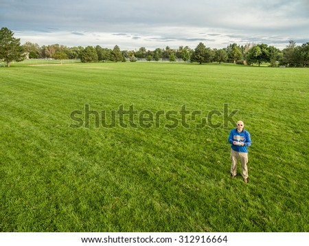 aerial shot of a male drone operator with a radio controller on a green grassy field - stock photo