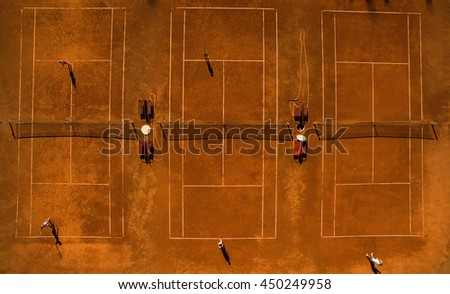 Aerial shot of a tennis courts with players in warm evening sunlight - stock photo