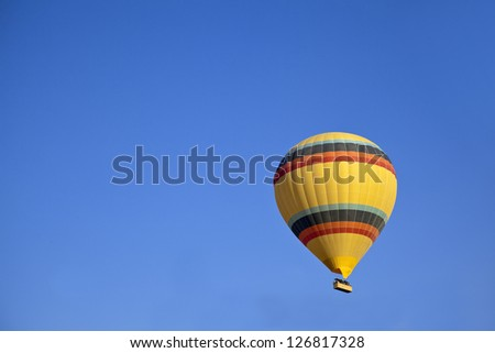 Aerial shot of yellow hot air balloon with colored bands in a clear blue sky. Generic image, shot location, Cappadocia, Anatolia, Turkey - stock photo