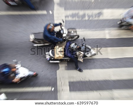 Aerial shot with a zoomed-out effect, of motorcyclists stopping at a zebra crossing in Bangkok, Thailand